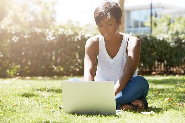 Young woman working outside on laptop computer.